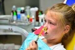 Uma menina está curando um dente em um dentista em uma recepção que senta-se em uma poltrona no escritório do ` s do doutor imagem de stock