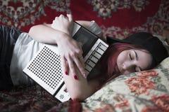 Uma menina está dormindo com um gravador velho da gaveta em suas mãos fotos de stock