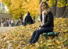 Uma menina está em um parque do outono Fotografia de Stock Royalty Free