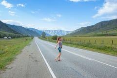 Uma menina está em uma estrada da montanha Imagens de Stock