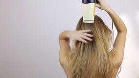 Uma menina está estando com sua parte traseira e está secando seu cabelo molhado vídeos de arquivo