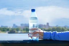 Uma menina está guardando uma garrafa da água em sua mão imagem de stock
