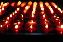 Uma menina está guardando a vela e está rezar-la perto do altar na igreja fotos de stock