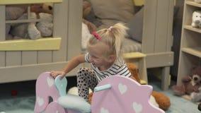 Uma menina está jogando um brinquedo em sua sala vídeos de arquivo