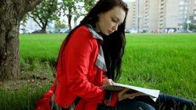Uma menina está lendo o assento na grama vídeos de arquivo