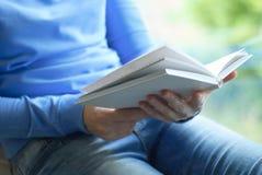 Uma menina está lendo um livro fotos de stock
