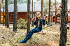 Uma menina está montando em um balanço no pátio de uma casa de campo Imagens de Stock Royalty Free