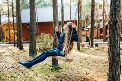 Uma menina está montando em um balanço no pátio de uma casa de campo Foto de Stock