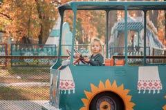 Uma menina está montando um carro em uma atração fotografia de stock