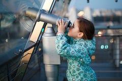 Uma menina está olhando através de um telescópio Imagens de Stock