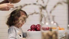 Uma menina está olhando como a tabela festiva é decorada A mulher põe as placas sobre a tabela do feriado video estoque