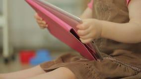 Uma menina está olhando desenhos animados em uma tabuleta eletrônica vídeos de arquivo