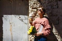 Uma menina está perto da parede urbana com uma xícara de café foto de stock royalty free