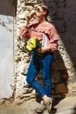 Uma menina está perto da parede urbana com uma xícara de café fotografia de stock