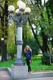 Uma menina está perto de uma lâmpada. Fotografia de Stock Royalty Free