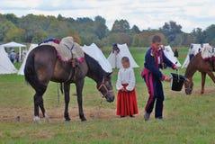 Uma menina está por um cavalo Imagem de Stock Royalty Free