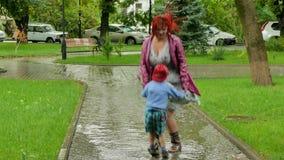 Uma menina está saltando com um menino em uma poça vídeos de arquivo