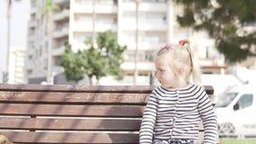 Uma menina est? sentando-se em um banco na cidade vídeos de arquivo
