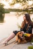 Uma menina está sentando-se fora na grama, agitando lovingly as mãos com seu cão, mostrado em silhueta contra o céu sunsetting imagens de stock