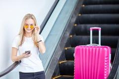 Uma menina está sentando-se no telefone no fundo de uma mala de viagem cor-de-rosa imagens de stock royalty free