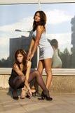 Uma menina está sentando-se oposto a outra Foto de Stock Royalty Free