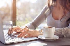 Uma menina está trabalhando em um portátil em um café em um dia ensolarado Fotos de Stock