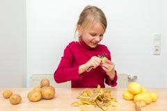 Uma menina está vestindo uma camiseta vermelha da gola alta Aprecia descascar batatas com um descascador e ri imagens de stock royalty free