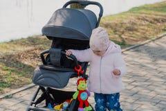 Uma menina est? rolando o transporte de beb? no parque Crian?a no parque que joga com pram imagens de stock royalty free