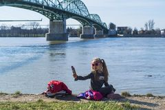 Uma menina est? sentando-se no banco do rio com um telefone Em um dia de mola morno Uma menina faz um selfie imagens de stock