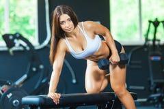 Uma menina executa um peso com a uma mão na inclinação usando um banco exercício nos músculos traseiros os mais largos com foto de stock royalty free