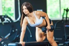 Uma menina executa um peso com a uma mão na inclinação usando um banco exercício nos músculos traseiros os mais largos com fotos de stock royalty free