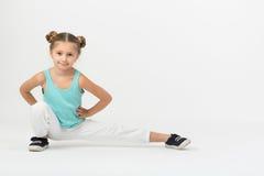 Uma menina faz o assento ginástico do exercício fotografia de stock royalty free