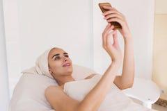 Uma menina faz o selfie em seu telefone em uns termas Foto de Stock Royalty Free