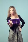 Uma menina feliz bonita com um presente. Foto de Stock