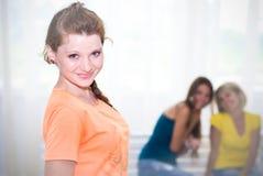 Uma menina feliz com aprovação, dois adolescentes na parte traseira Foto de Stock