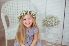 Uma menina feliz com uma grinalda floral está sorrindo Imagens de Stock