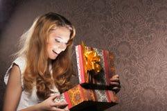 Uma menina feliz do teenge que abre um presente de Natal Fotos de Stock Royalty Free