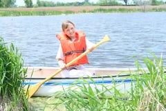 Uma menina feliz em uma canoa. Imagem de Stock