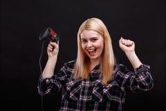 Uma menina feliz está guardando um manche do jogo Em um fundo preto imagem de stock