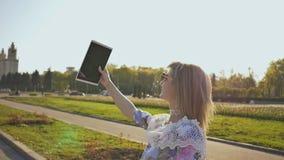 Uma menina feliz faz o selfie com uma tabuleta em uma noite morna no por do sol vídeos de arquivo