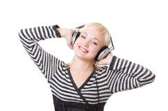 Uma menina feliz na música de escuta dos auscultadores Fotografia de Stock