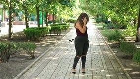Uma menina feliz nova com caminhadas do peso adicional em um parque do verão Modelo positivo do tamanho video estoque