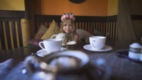 Uma menina feliz pequena está sentando-se no sofá em um café e está abraçando-se seu coelho enchido filme