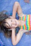 Uma menina feliz que coloca na associação de água. Foto de Stock