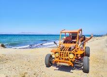 Uma menina feliz que conduz um carrinho em uma duna da praia Console de Kos sul foto de stock royalty free