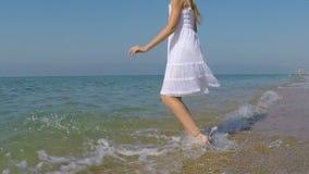 Uma menina feliz que joga na praia vídeos de arquivo
