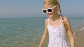 Uma menina feliz que joga na praia filme