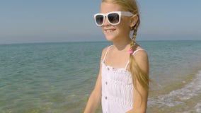Uma menina feliz que joga na praia video estoque