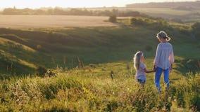 Uma menina fresca pequena com cabelo louro mostra a mamã um por do sol bonito sobre campos verdes filme