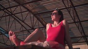 Uma menina grávida bonita em um roupa de banho de uma peça só vermelho e em vidros senta-se em um vadio do sol video estoque